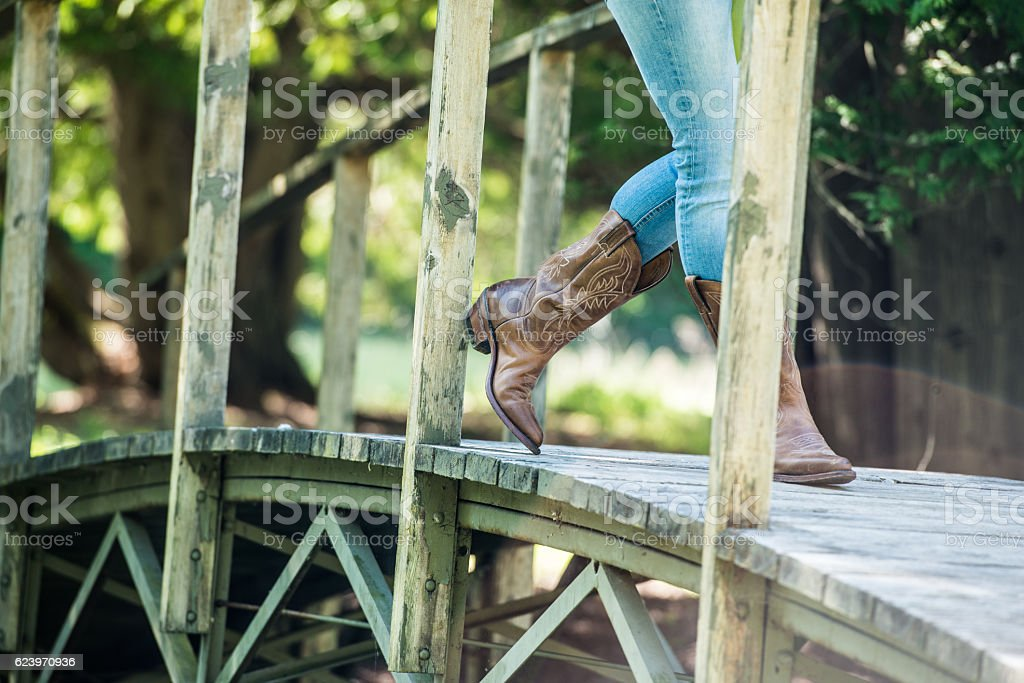 Girl holding Peony with focus on Boots stock photo
