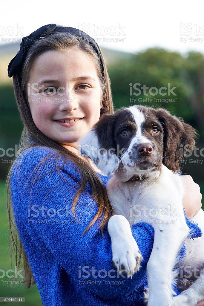 Girl Holding Pet Spaniel Puppy Outdoors In Garden stock photo