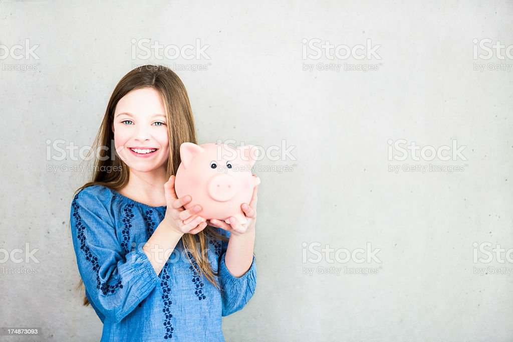 Girl holding piggy bank looking into camera royalty-free stock photo