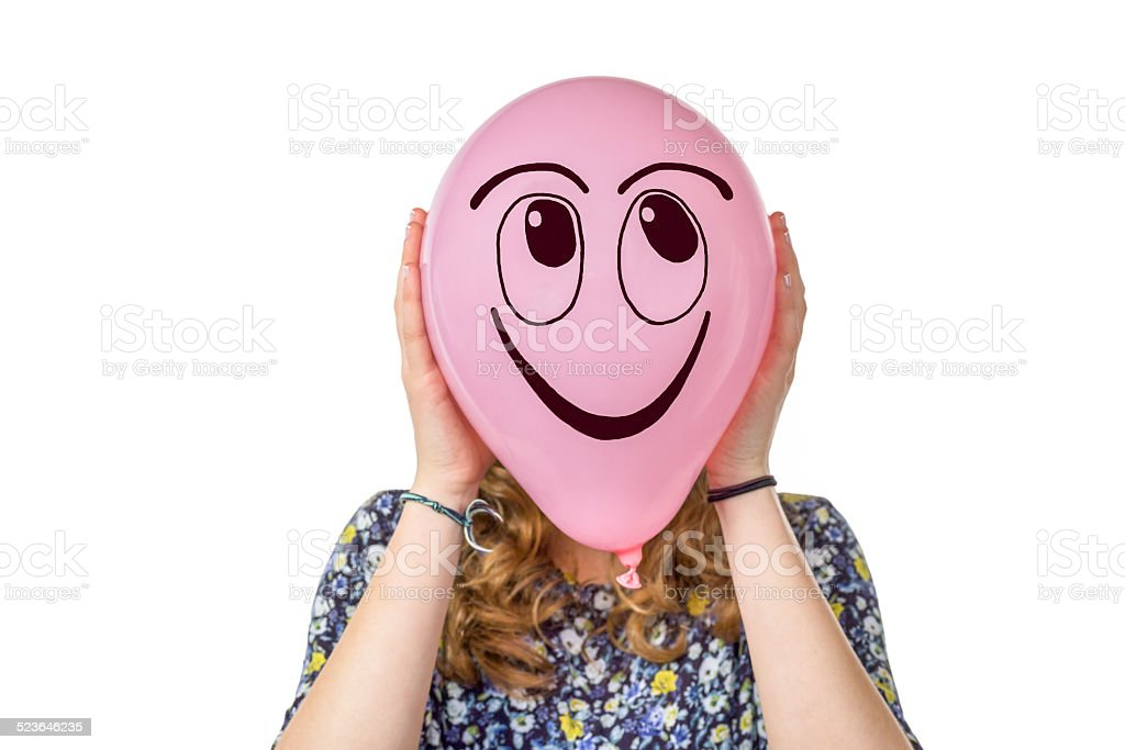 Girl holding pink balloon with smiling face stock photo
