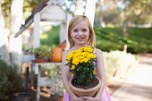 Girl holding potted plant outdoors