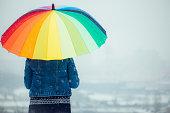 Girl holding rainbow umbrella