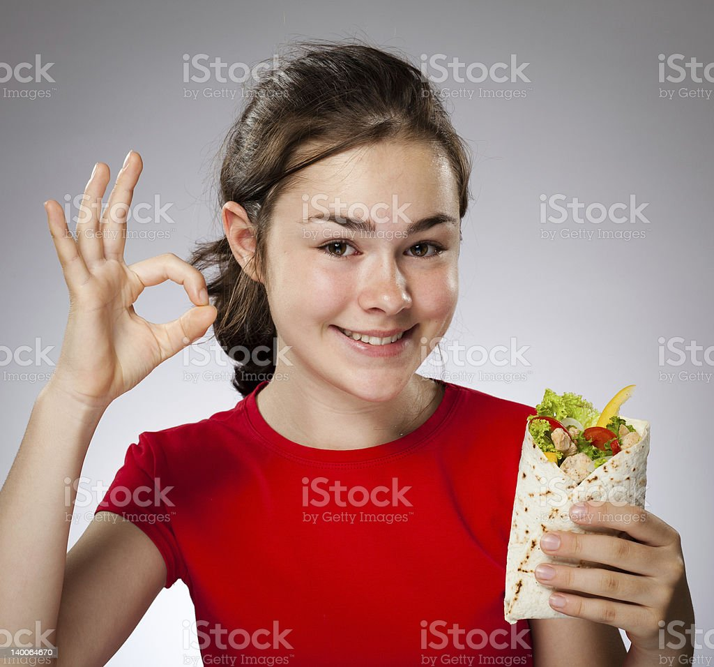 Girl holding sandwich showing OK sign royalty-free stock photo