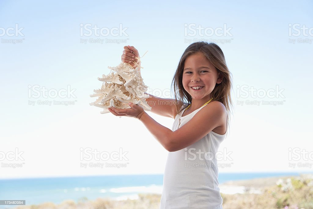 Girl holding shell necklace on beach stock photo