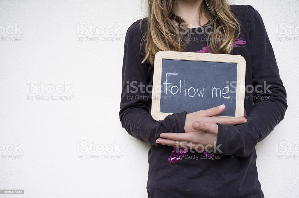 Girl holding sign with Follow me royalty-free stock photo