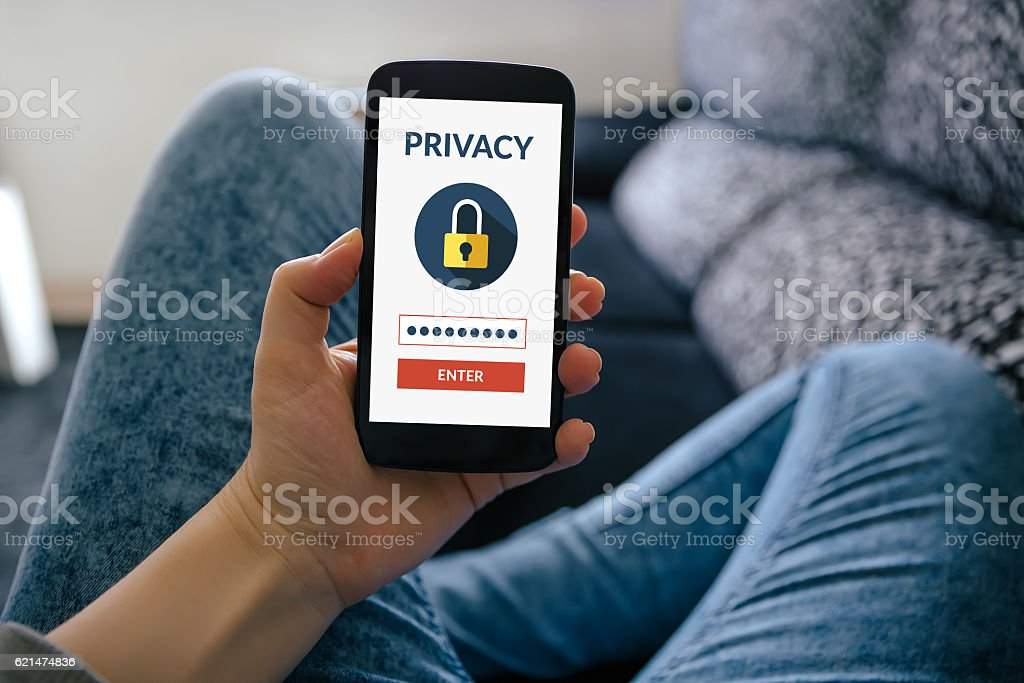 Girl holding smart phone with online privacy concept on screen stock photo