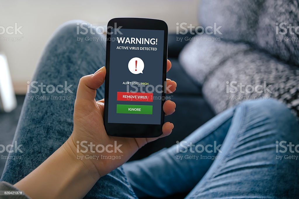 Girl holding smartphone with virus alert on screen stock photo