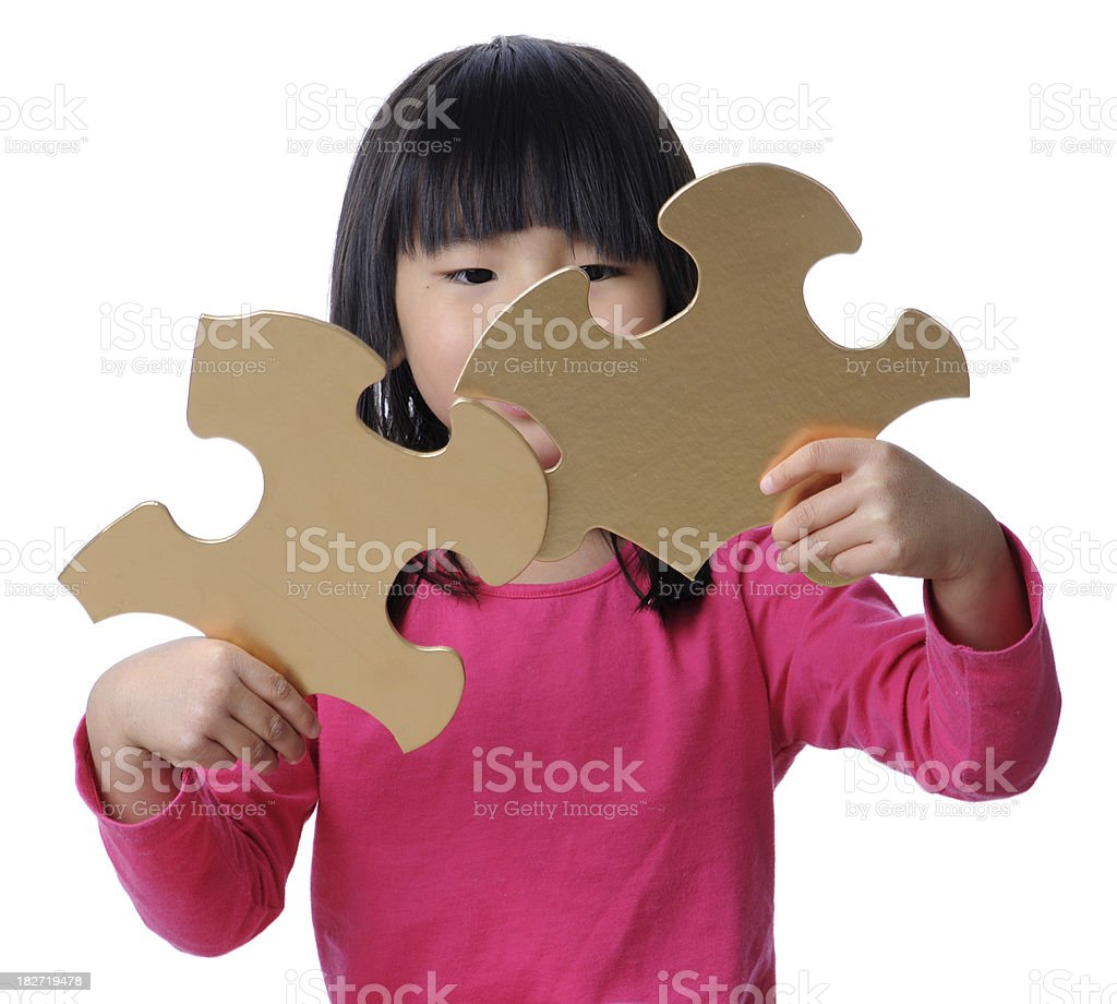 Girl Holding Two Gold Puzzle Pieces royalty-free stock photo