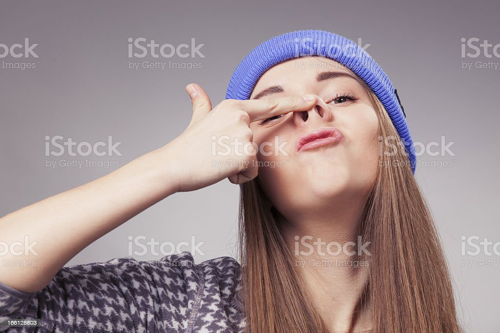 girl holding up fingers on nose and making silly expression royalty-free stock photo