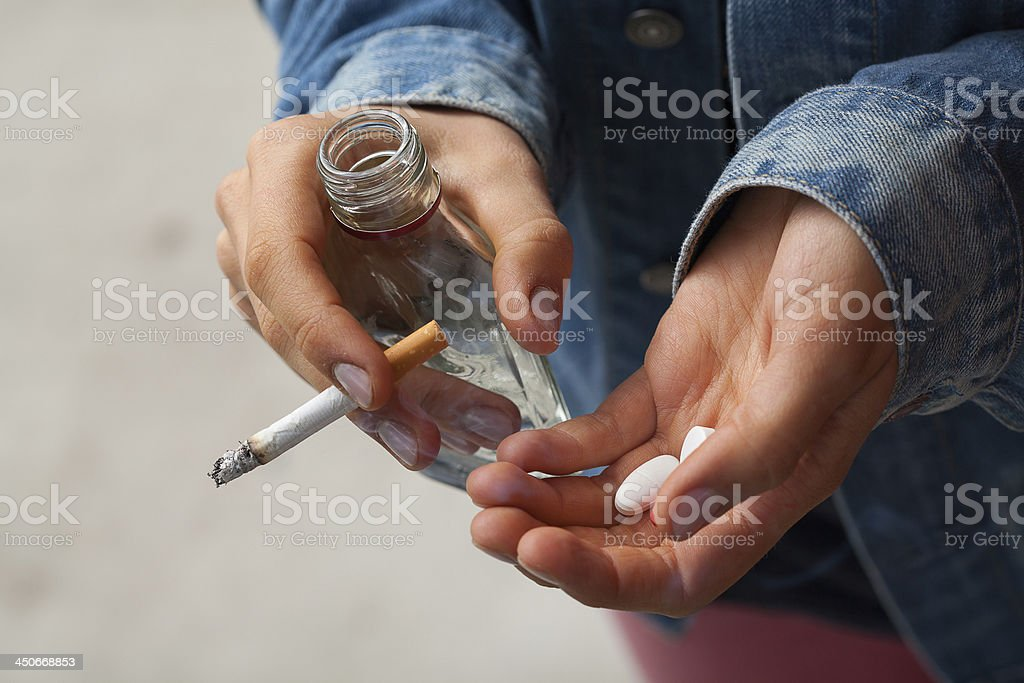 Girl holding vodka,pills and cigarettes stock photo