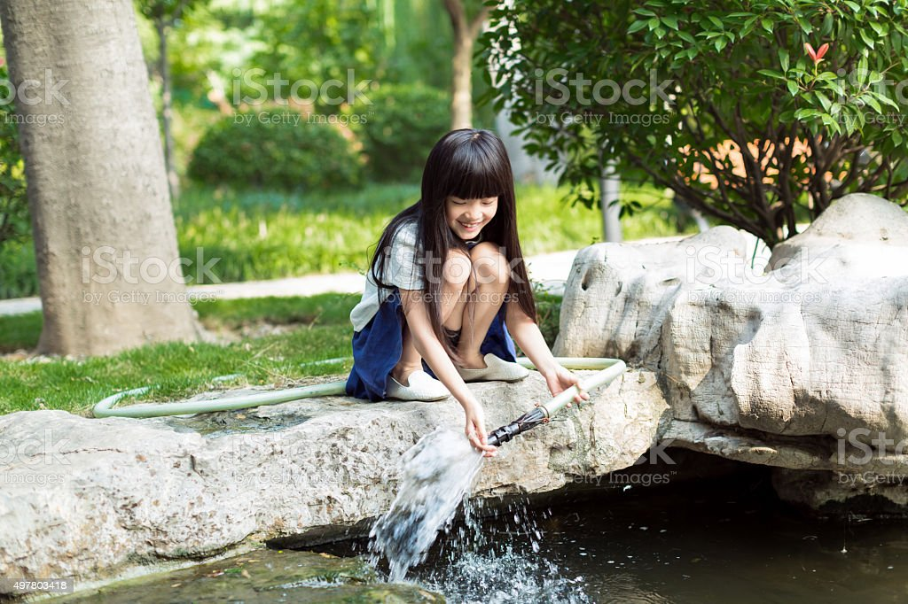 girl holding water pipe stock photo