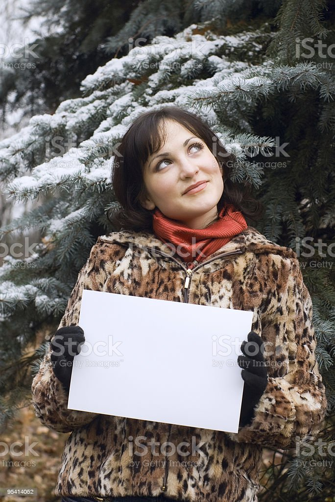 girl holding white card with snow on the background royalty-free stock photo