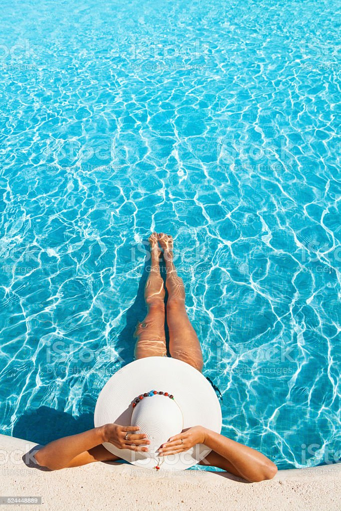 Girl holding white hat with hands in swimming pool stock photo