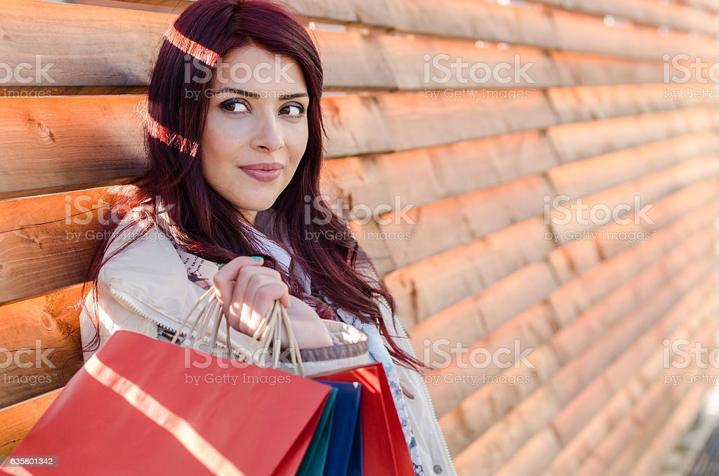 Girl holds a bags over the shoulder and looking side. stock photo