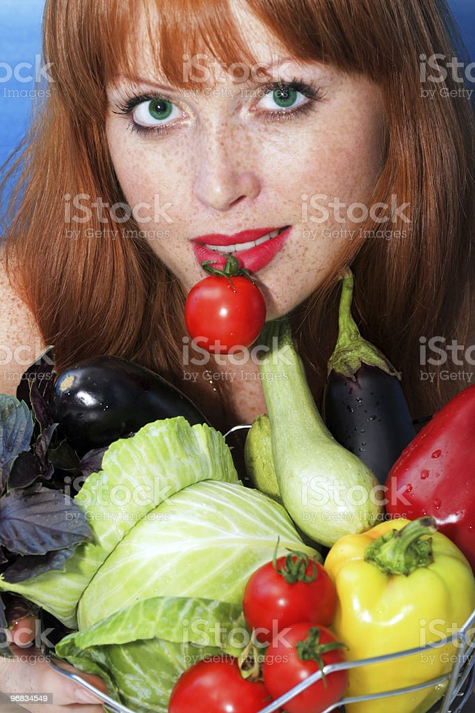 girl holds by teeth a small tomato royalty-free stock photo