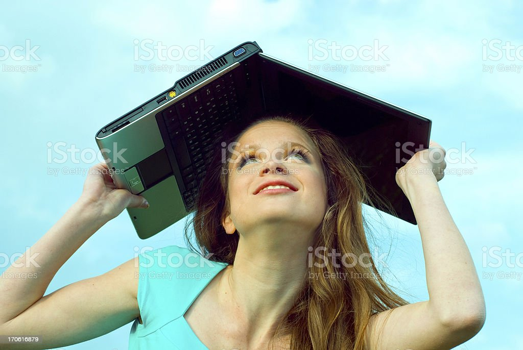 girl holds computer above a head stock photo