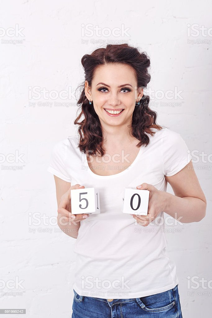 Girl holds in hands number fifty. stock photo