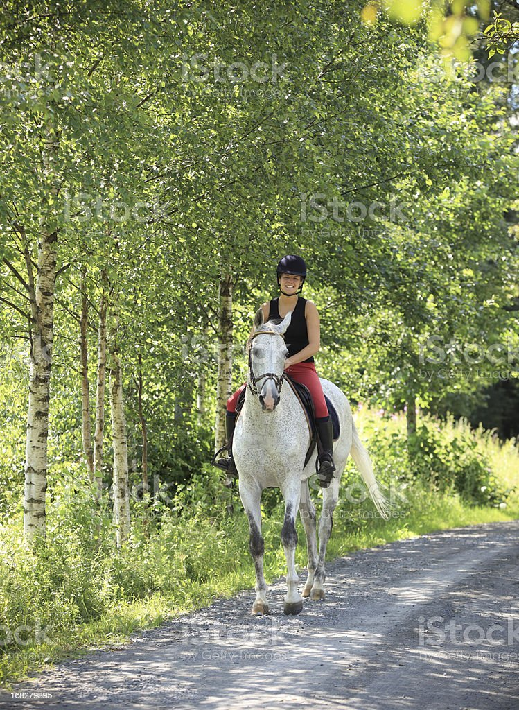 Girl horseback riding in the forest, Norway stock photo