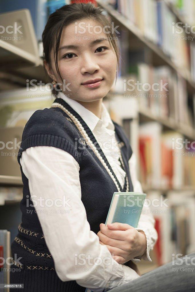 Girl huggering a book near bookshelf royalty-free stock photo