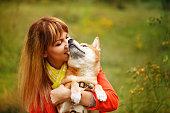 Girl hugging dog Shiba Inu in autumn park.