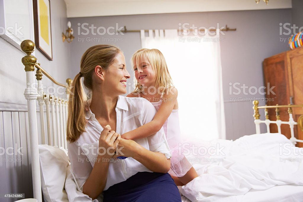 A girl hugging her mother as she gets ready for work stock photo
