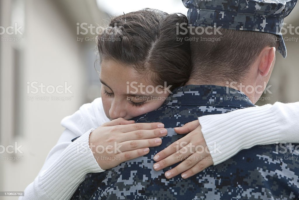 Girl hugging military dad stock photo