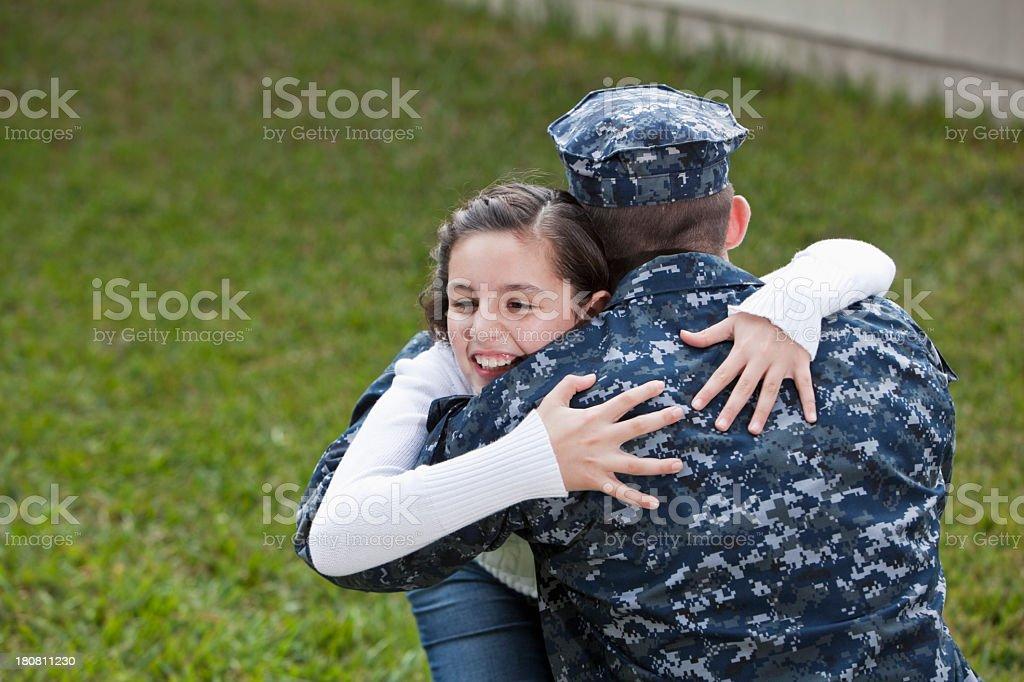 Girl hugging military dad stock photo