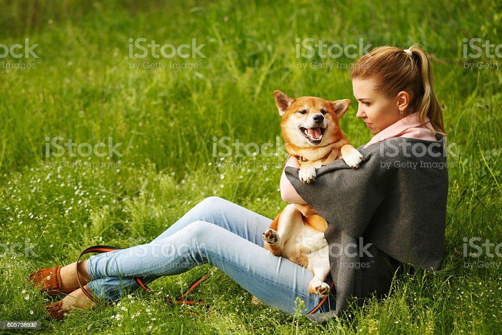 Girl hugs dog Shiba Inu. stock photo