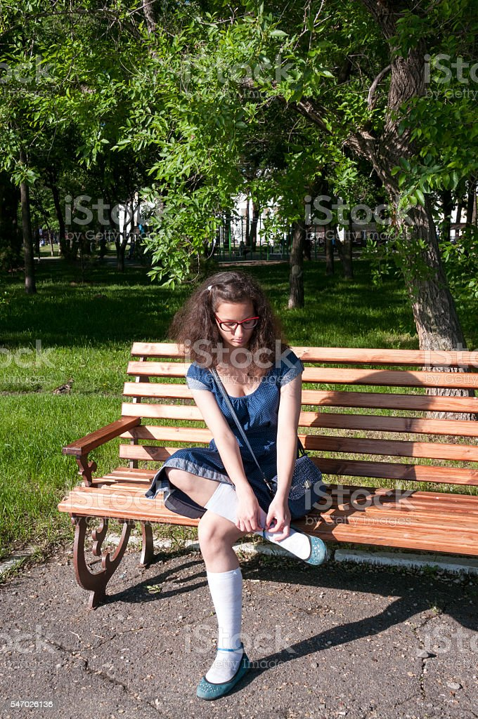 Girl in a blue dress sitting on a wooden bench stock photo