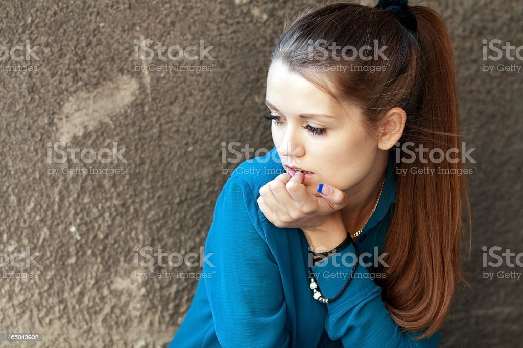 A girl in a blue shirt sitting against a concrete wall stock photo