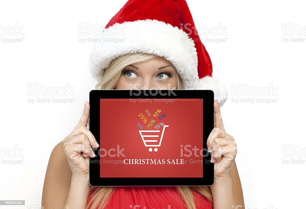 girl in a Christmas hat on New Year holding tablet royalty-free stock photo