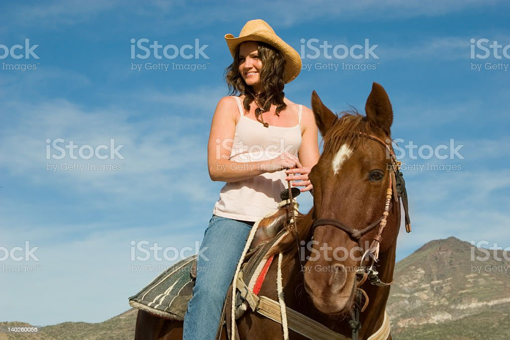 Girl in a cowboy hat riding a horse stock photo