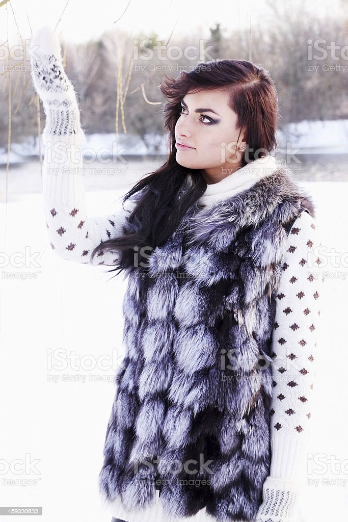 girl in a fur vest catches snow stock photo