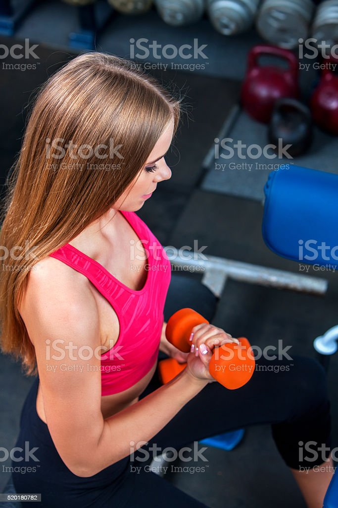 Girl in a gym, shakes  muscles hands. Biceps foreground stock photo