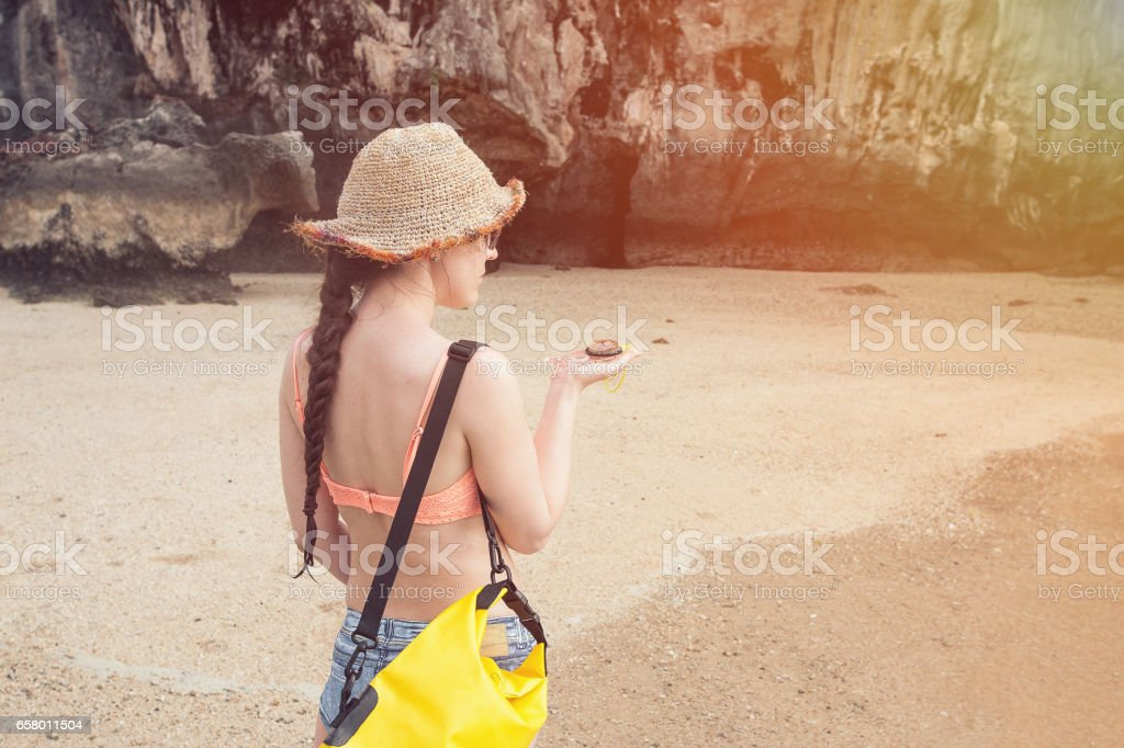girl in a hat and a bag is guided by the compass on the beach in Thailand stock photo