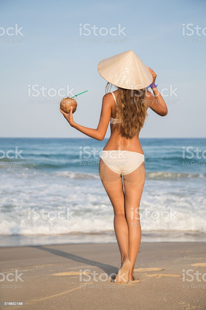 girl in a hat on the beach with a cocktail stock photo
