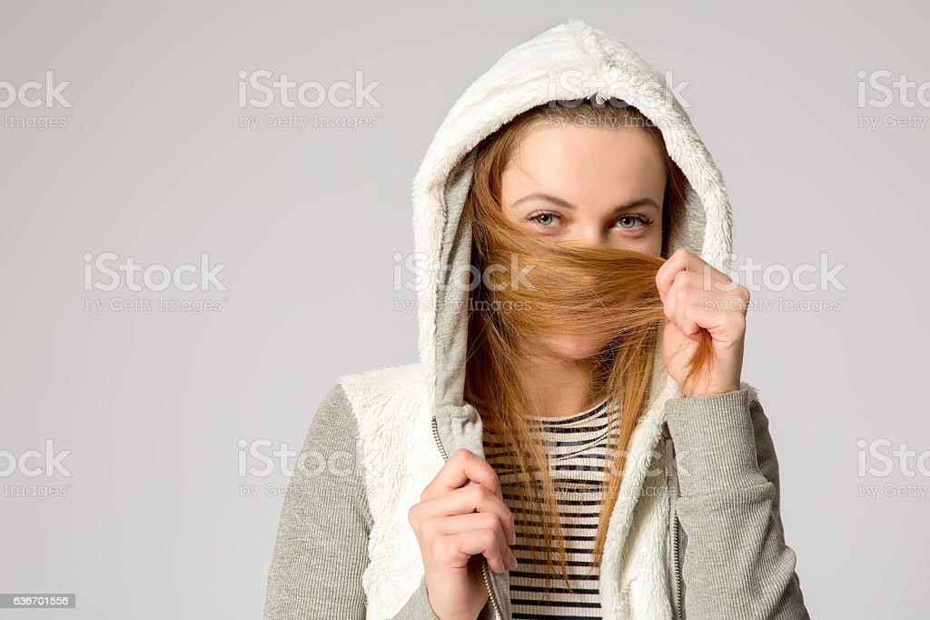 girl in a hood hides her face in her hair stock photo