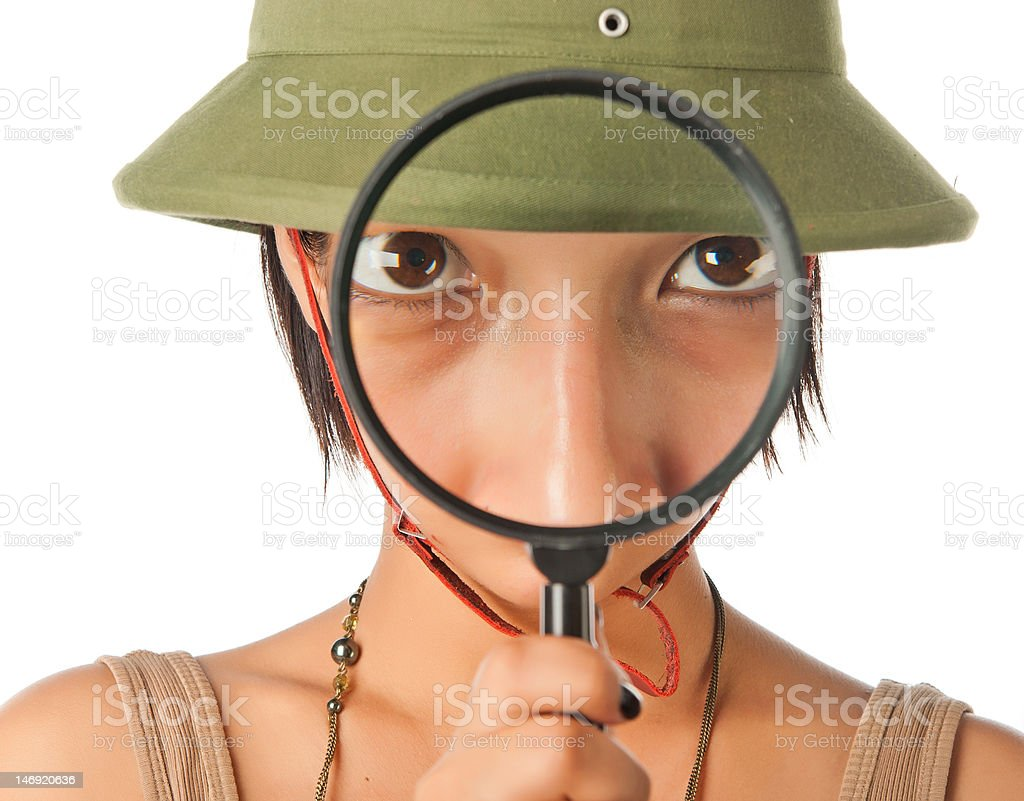 Girl in a pith helmet looks throught magnifier stock photo