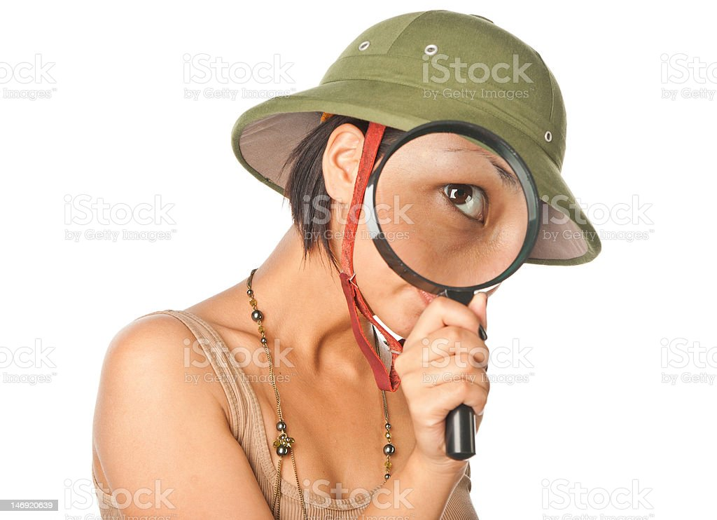 Girl in a pith helmet looks throught magnifier royalty-free stock photo