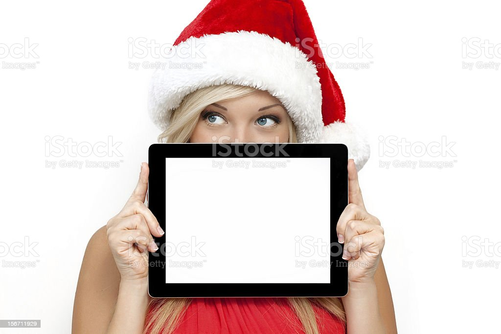 girl in a red Christmas hat, holding tablet touch royalty-free stock photo