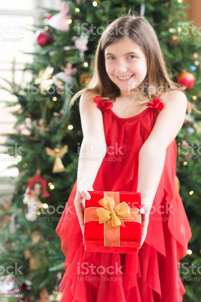 girl in a red dress holds out a wrapped gift stock photo