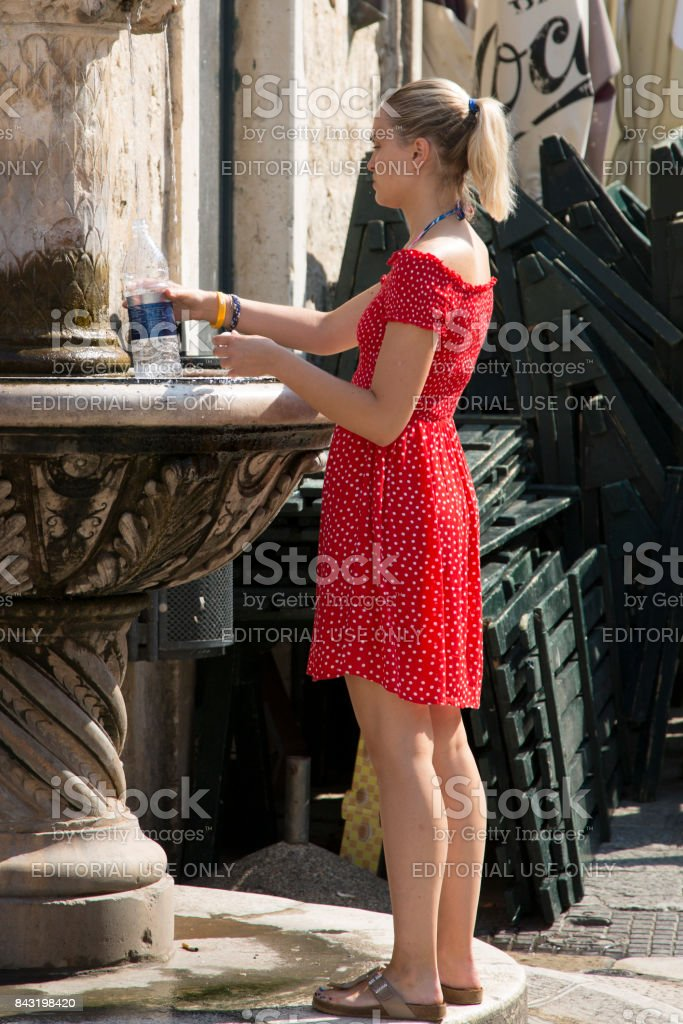 Girl in a red dress is picking up water. Hot summer of 2017 in Dubrovnik, Croatia. stock photo