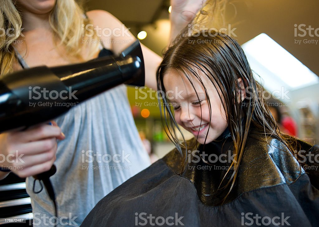 A girl in a salon getting her hair done with a blow dry stock photo