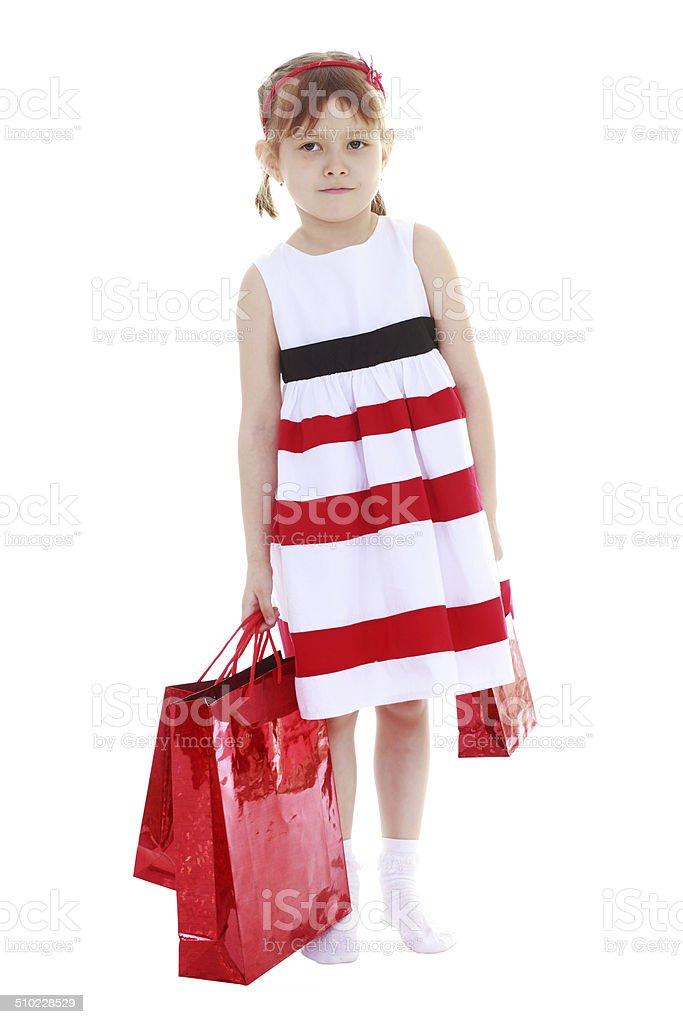 Jeune fille dans une robe rayée en tenant rouge paquets photo libre de droits