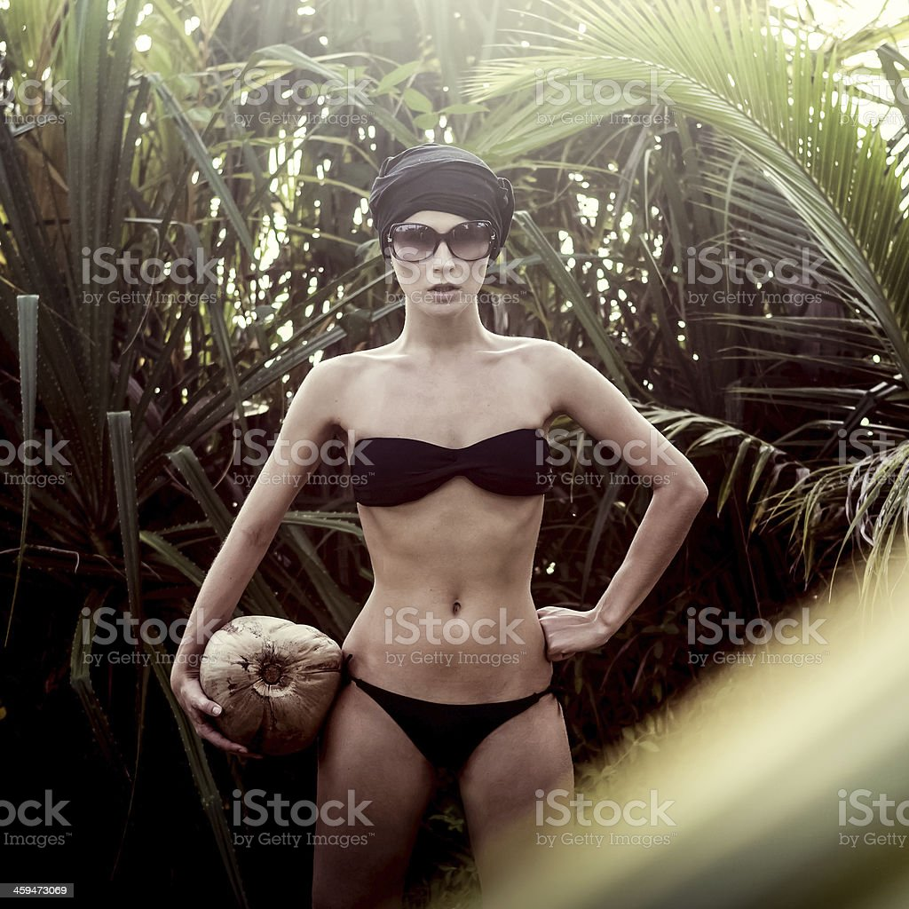 girl in a tropical jungle with coconut stock photo