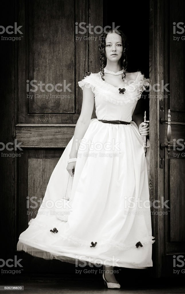 Girl in a vintage dress coming out of doors stock photo