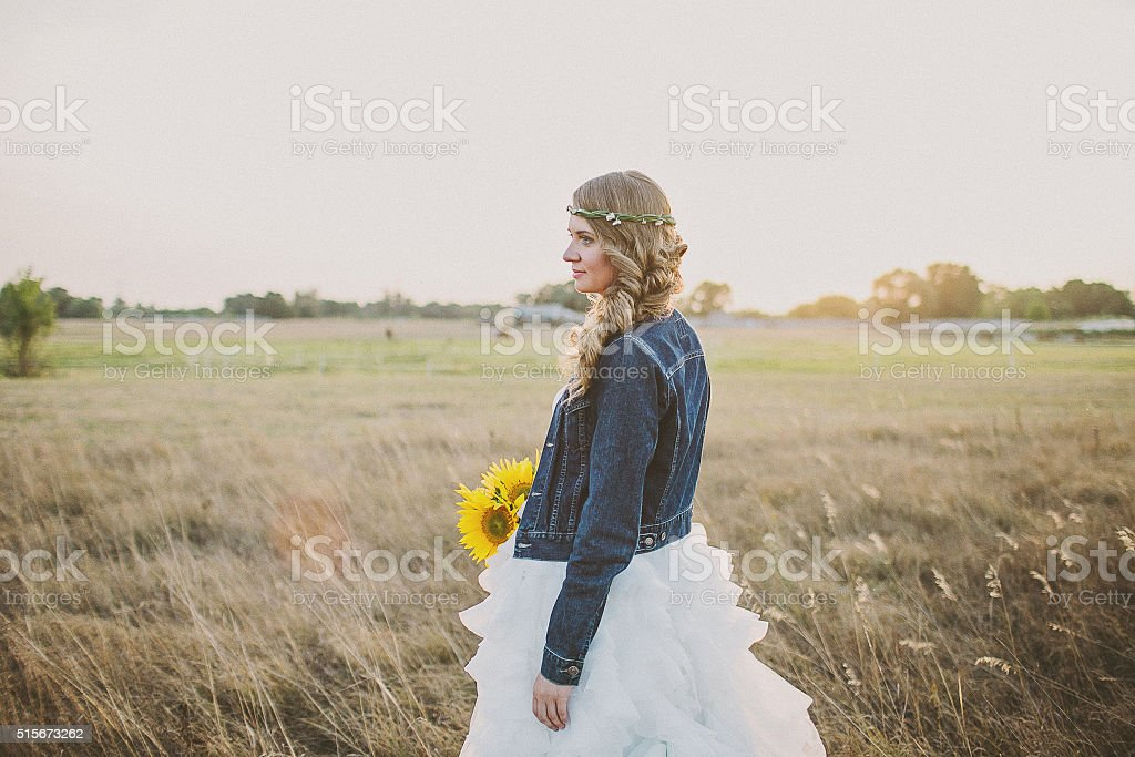 Girl in a wedding dress and jeans jacket with sunflowers stock photo