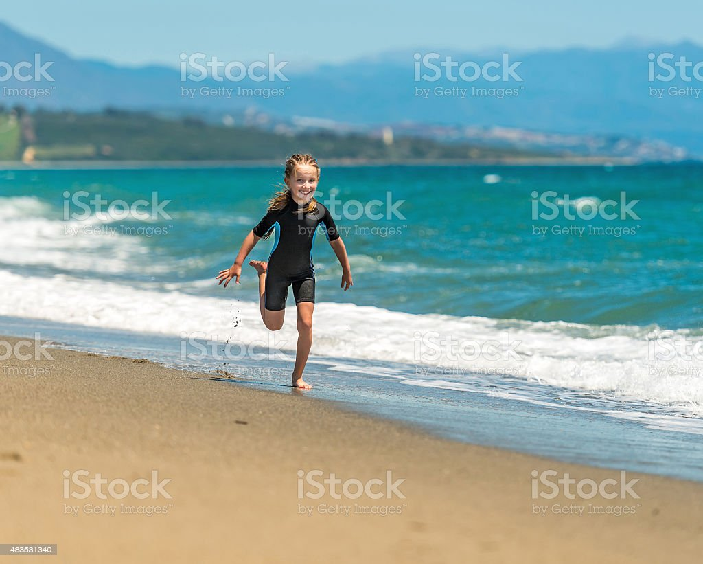 girl in a wetsuit running along the beach stock photo