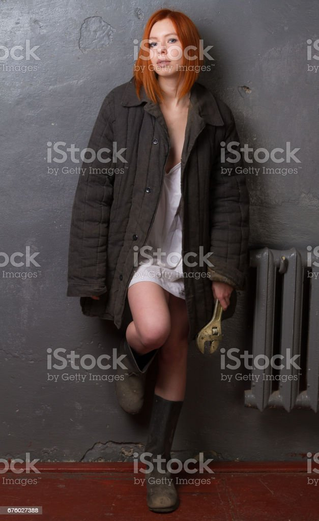 Girl in a worker suit on a gray background. stock photo