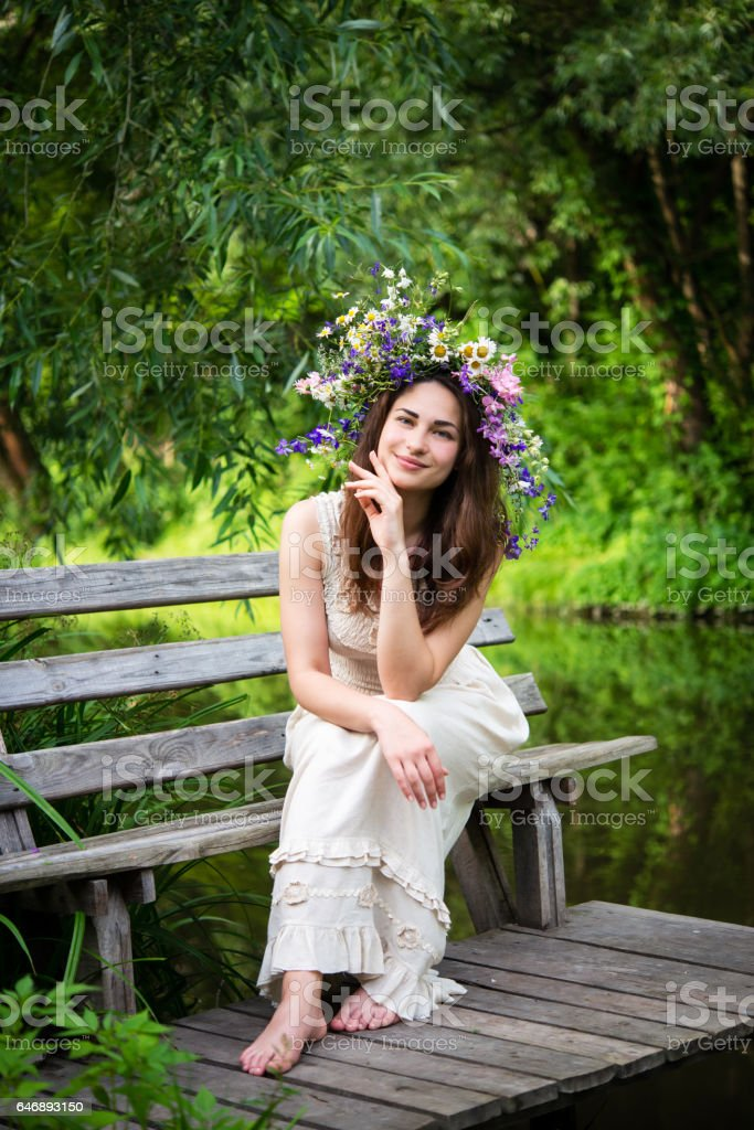 girl in a wreath sitting on a bench leaning on elbows stock photo